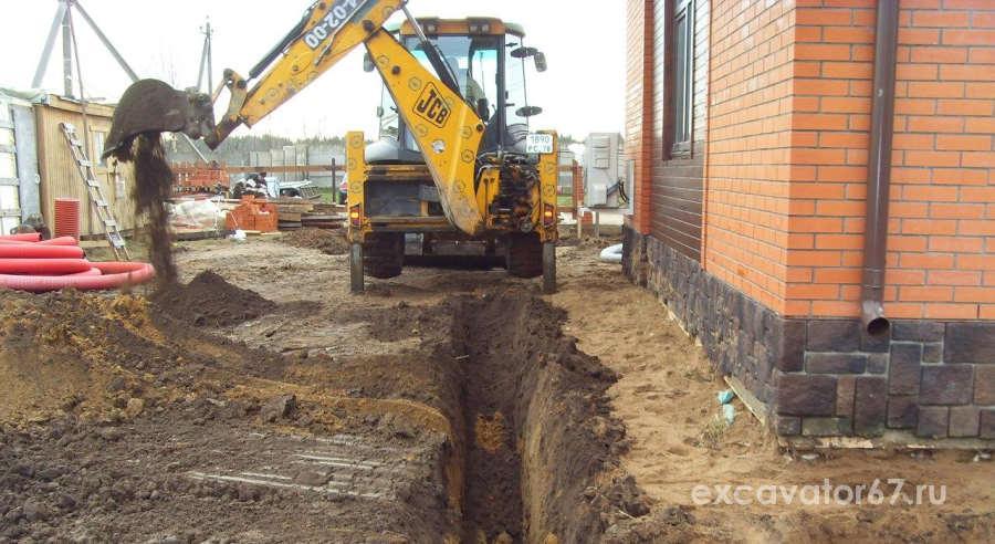 экскаватор копает канализацию